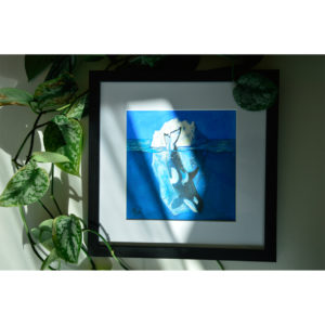 Framed painting of a killer whale into the blue and iceberg behind.