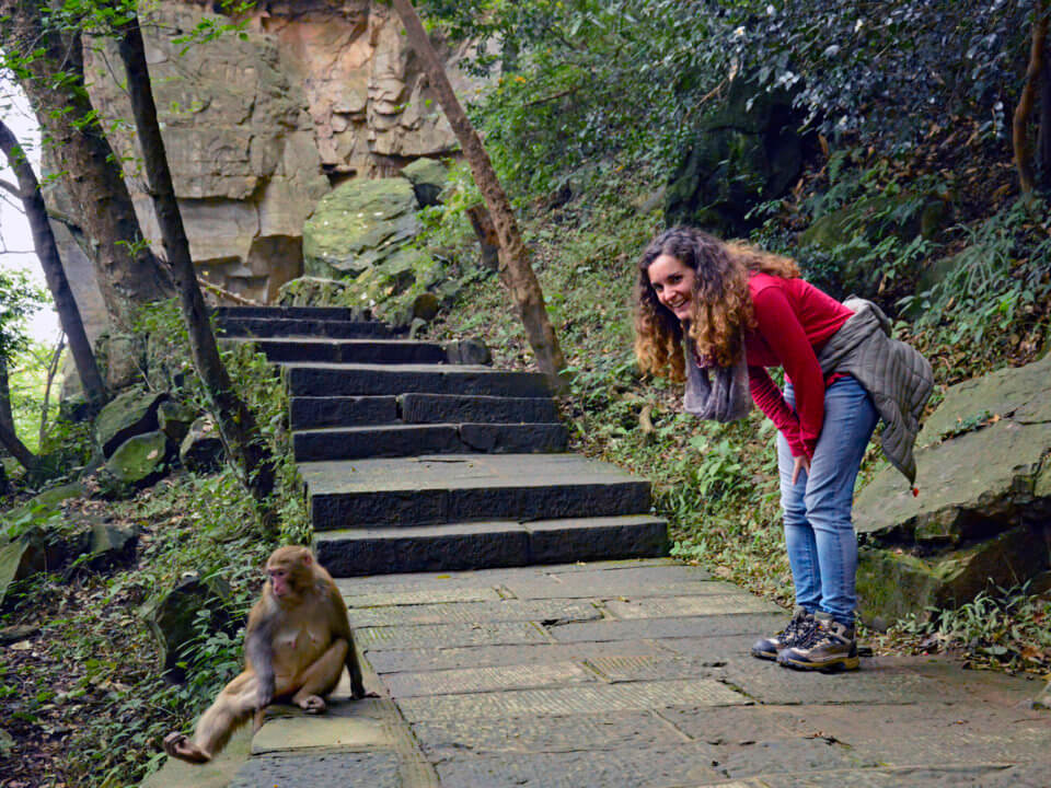 Blogger posing with a macaque on the hiking trail in Zhangjiajie, China.
